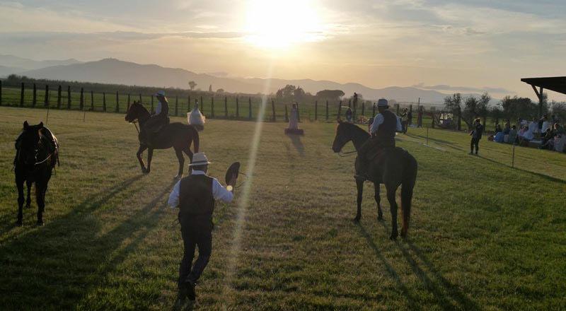 Foto di butteri al tramonto classici cowboy della maremma toscana