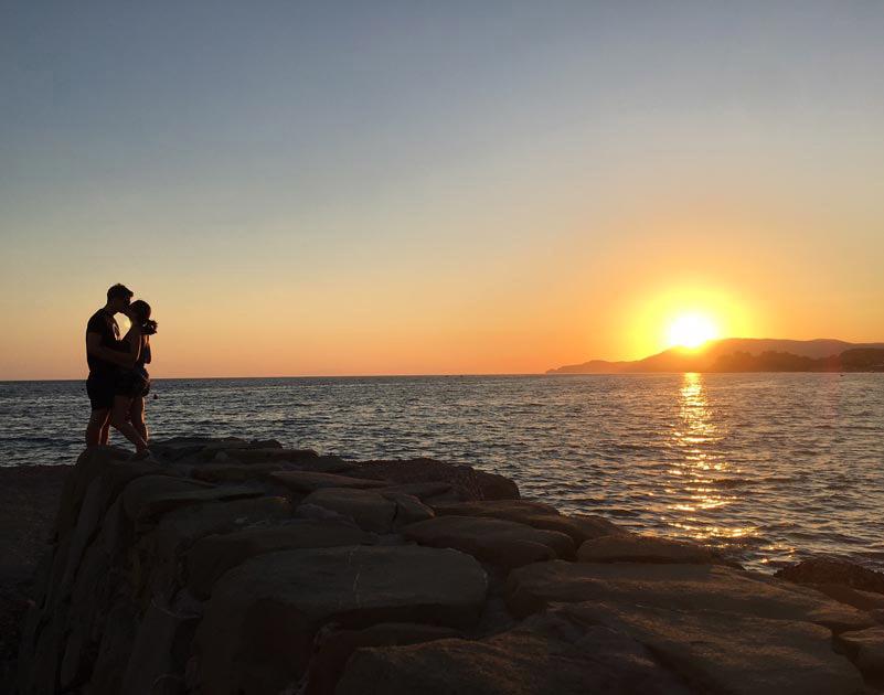 Foto di coppia che si bacia al tramonto sul mare in toscana